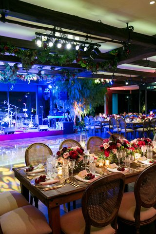 wood-reception-table-and-chairs-low-red-flower-arrangements-candles-next-to-bright-lights-on-dance