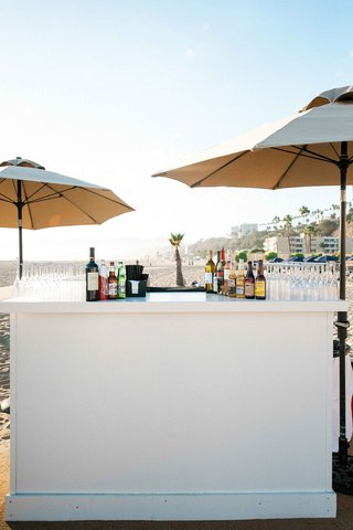wedding-cocktail-hour-bar-under-tan-umbrellas-at-the-jonathan-club-santa-monica