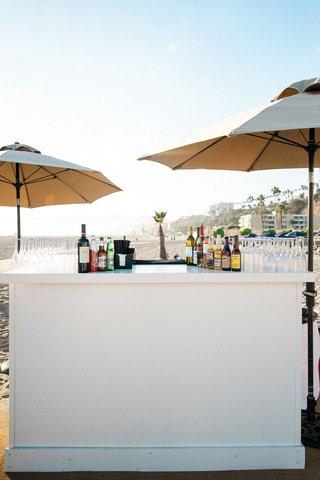 wedding-cocktail-hour-bar-under-tan-umbrellas-at-the-jonathan-club-santa-monica