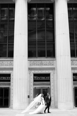 black and white photo of bride in strapless wedding dress and veil tuxedo wintrust chicago building