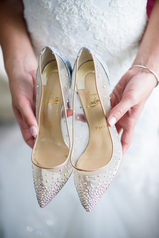 bride-holding-christian-louboutin-bridal-heels-pointed-toe-clear-with-rhinestone-details