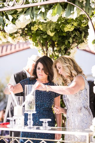 mother-of-groom-and-mother-of-bride-lighting-candles-in-hurricane-vases-on-crystal-stands-ceremony