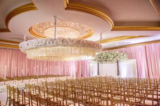 wedding-ceremony-ballroom-gold-chairs-white-orchid-flower-suspended-from-ceiling-chandelier-taper