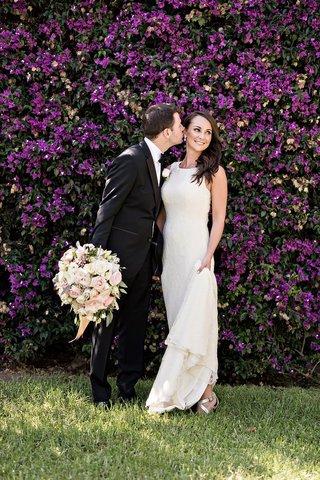 groom-going-to-kiss-bride-cheek-black-tuxedo-white-sheath-gown-pastel-bouquet