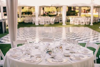 white-reception-tent-with-tables-covered-in-white-tablecloths-surrounded-by-white-chairs