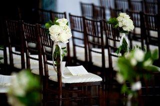 wedding-ceremony-with-dark-chiavari-chairs-white-cushions-white-roses-greenery-white-ribbons