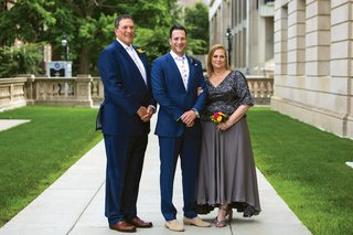 groom-on-sidewalk-standing-in-between-his-father-in-navy-suit-mother-in-grey-dress-small-nosegay