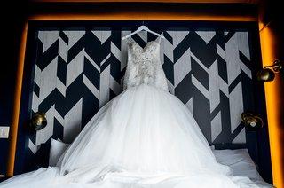 wedding-dress-on-white-hanger-embellished-beaded-bodice-with-full-skirt-on-headboard