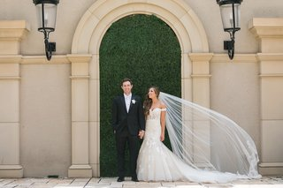 bride-in-stella-york-lace-mermaid-gown-cathedral-veil-with-lace-groom-in-suit