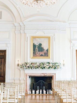 wedding-ceremony-gold-chairs-altar-fireplace-fresh-flowers-sconces-artwork-oheka-castle-wedding