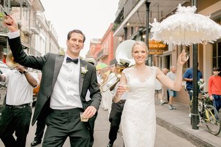 bride-in-an-off-the-shoulder-reem-acra-lace-dress-holds-white-feathered-umbrella-groom-in-black-tux