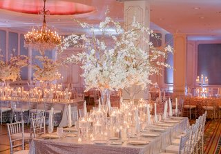 silver-linens-on-table-with-lots-of-floating-candles-and-tall-white-flower-on-branch-centerpiece