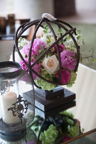 pink-flower-cream-rose-greenery-in-branch-sphere-on-table-at-wedding