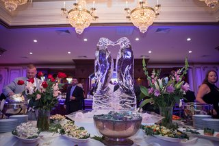 ashley-alexiss-reception-cocktail-hour-food-ice-bar-with-ice-sculpture-of-penguins-purple-lighting