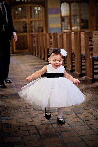 adorable-little-girl-toddler-in-a-black-and-white-dress-with-a-flower-headband-runs-through-church