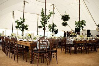 tented-wedding-reception-with-country-tables-branches-with-leaves-on-posts-and-greenery-chandelier