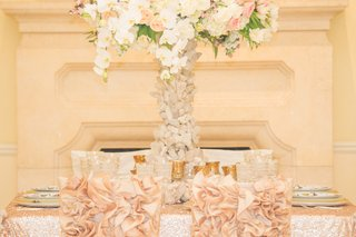 wedding-reception-with-pink-and-white-flowers-on-quartz-stand-pink-chair-sleeves-with-ruffles