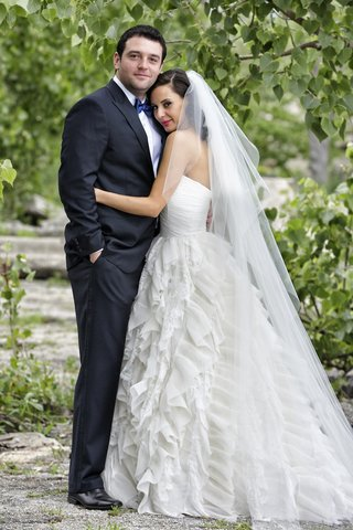bride-in-ruffle-wedding-dress-with-groom-in-tuxedo