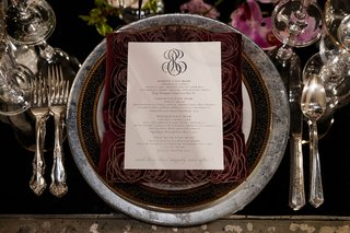 wedding-menu-framed-by-dark-laser-cut-rose-pattern-on-charger-plate-with-black-and-grey-marble-rim