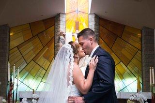 bride-groom-first-kiss-catholic-church-walnut-california-long-veil-stained-glass