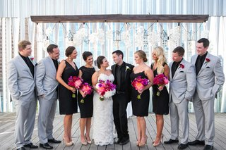 bridesmaids-in-black-cocktail-dresses-and-groomsmen-in-grey-suits-look-in-at-newlywed-couple