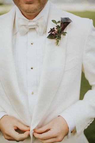 groom-in-white-tuxedo-jacket-bow-tie-gold-buttons-dark-burgundy-calla-lily-boutonniere-greenery