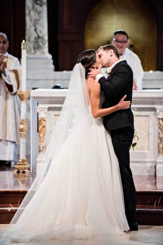 catholic-wedding-ceremony-bride-and-groom-kiss-bride-in-reem-acra-ball-gown