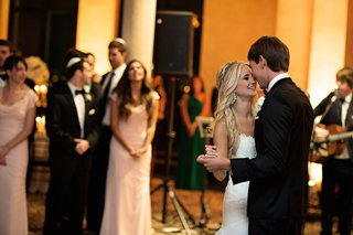 bride-in-a-strapless-romona-keveza-gown-dances-with-groom-in-a-black-tuxedo