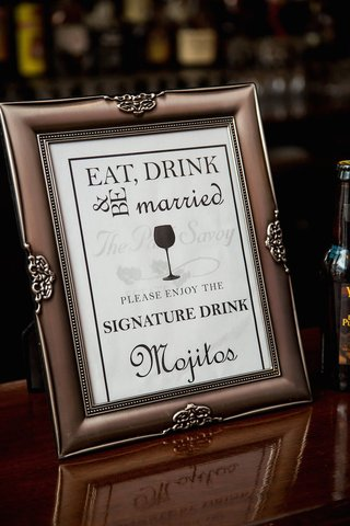 wedding-reception-bar-sign-in-a-coppertone-frame-listing-mojitos-as-the-nights-signature-drink