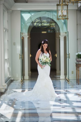 a-bride-in-a-stunning-white-trumpet-gown-with-a-train-glances-at-her-bouquet-white-flowers-foliage