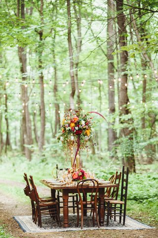 wedding-reception-country-table-surrounded-by-mismatched-wooden-chairs-on-an-oriental-rug