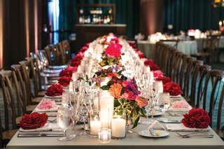 long-wedding-reception-table-with-small-floral-arrangements-and-pillar-candles-down-the-center