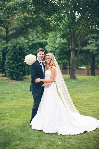 young-couple-in-wedding-attire-on-grass-lawn