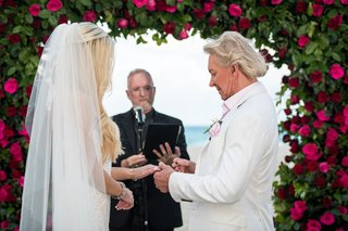 bride-with-long-blonde-hair-and-veil-groom-in-white-jacket-pink-shirt-putting-ring-on-brides-finger