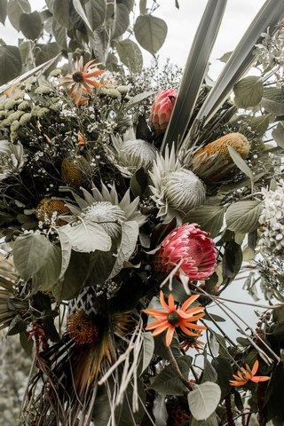 protea-wedding-flowers-bright-pink-and-orange-flower-decor-at-wedding-ceremony-boho-chic