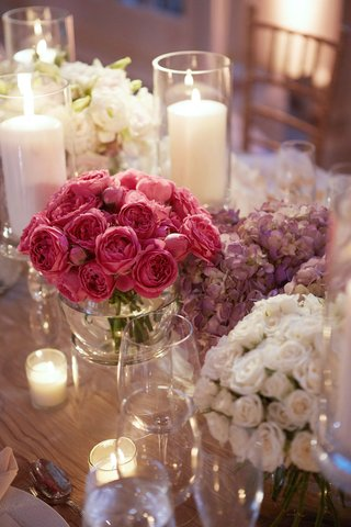 pillar-candles-in-hurricane-vases-separate-arrangement-of-pink-purple-and-white-centerpiece-design