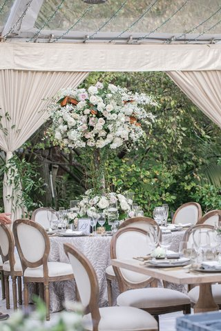 white-french-upholstered-chairs-around-round-and-wood-tables-tall-centerpiece-drapery-clear-tent