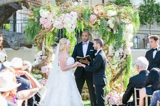 bride-and-groom-under-ceremony-structure-with-branches-and-flowers-with-friend-as-officiant