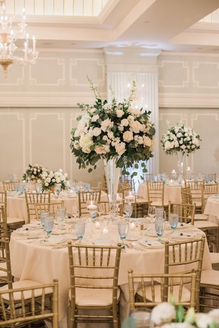 wedding-centerpiece-with-white-roses-and-greenery-pale-blue-glasses-gold-chiavari-chairs