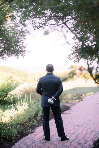 groom-holding-gift-behind-back-while-waiting-for-the-first-look