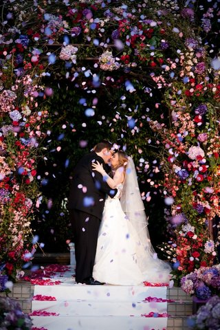 bride-and-groom-kissing-under-floral-canopy