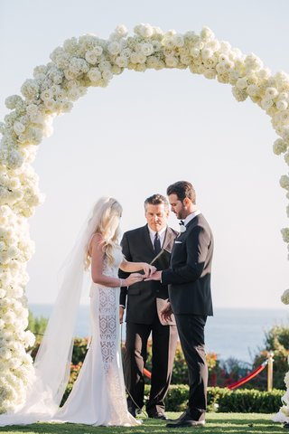 seaside-wedding-ceremony-with-bride-in-a-galia-lahav-dress-with-lace-panels-groom-in-black-tux