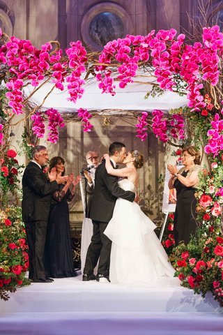 bride-and-grooms-first-kiss-at-wedding-ceremony-with-flower-embellished-chuppah-and-orchids