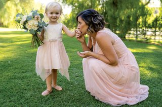 toddler-falower-girl-with-blush-skirt-holding-bouquet-bridesmaid-kisses-flower-girls-hand