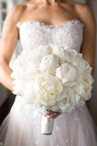 bride-in-strapless-wedding-dress-and-white-manicure-nails-holding-white-bouquet-of-peony-flowers