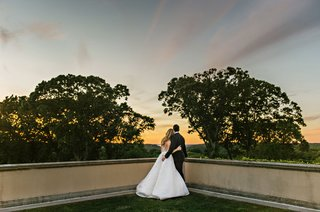 wedding-photo-bride-and-groom-looking-at-sunset-from-balcony-at-oheka-castle-angel-sanchez-tuxedo