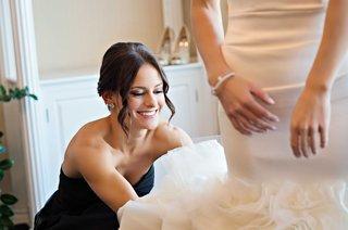 smiling-bridesmaid-in-black-dress-helps-bride-into-her-mermaid-style-wedding-dress