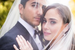 couple-portrait-wedding-photo-under-brides-veil-solitaire-diamond-engagement-ring-soft-makeup