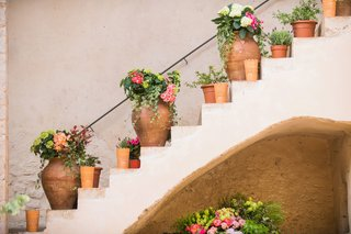 wedding-reception-abbey-courtyard-stone-stairs-terracotta-planter-vase-pink-flowers-greenery-lantern