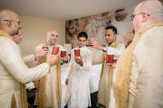 groom-groomsmen-cheers-hotel-room-indian-hindu-wedding-drinking-celebrating-traditional-friends